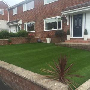 Front lawn laid with artificial turf, striped