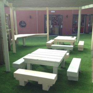 Artificial grass installed underneath picnic tables